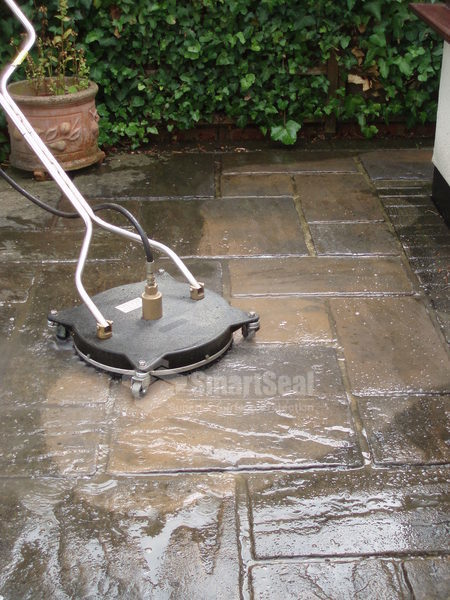 Rotary head power washer cleaning paving slabs